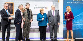 Vor dem E-Haus des ZVEH (v. l. n. r.): Hans-Georg Krabbe (ABB AG), Achim Berg (Bitkom), Anja Karliczek (Bundesministerin für Bildung und Forschung), Markus Söder (Bayerischer Ministerpräsident), Bundeskanzlerin Dr. Angela Merkel, Bundeswirtschaftsminister Peter Altmaier und Ingeborg Esser (GdW) Bild: Wirtschaftsinitiative Smart Living / Lena Siebrasse