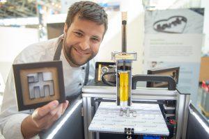 Schokolade aus dem 3D-Drucker: Buchstaben, ganze Sätze oder auch das IHM-Logo stellt Konditormeister Benedikt Daschner aus feinster Schweizer Schokolade her – mit Hilfe eines 3D-Druckers. Foto: GHM